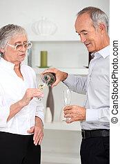 Elderly couple drinking champagne