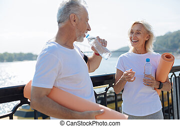 Elderly couple drinking water after yoga practice