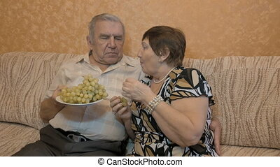 Elderly couple eating grape berries.