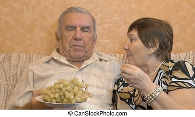 Elderly couple eating grape berries. They feed each other. Happy time.