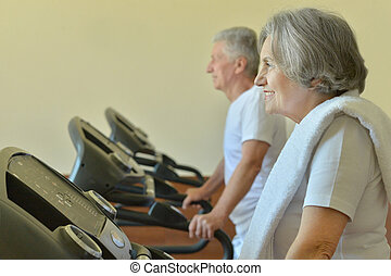 Elderly couple exercising in gym - Portrait of elderly...