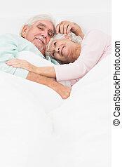 Elderly couple having a cuddle