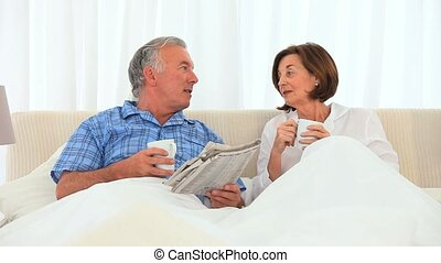 Elderly couple having a cup of tea in the bed