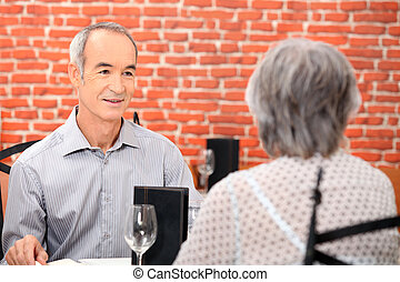 Elderly couple having meal in restaurant