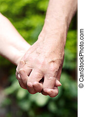 Elderly couple holding hands.