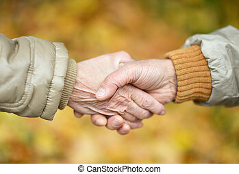 couple holding hands in autumn park