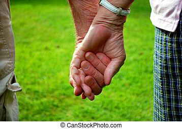 holding hands - elderly couple holding hands in front of...