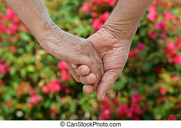 couple holding hands - Elderly couple holding hands over...
