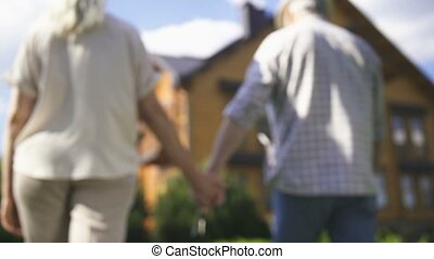Close-up of elderly couple's hands holding house door key and walking together on frontyard green lawn towards their new big dream house. Happy senor couple retired and purchased new home