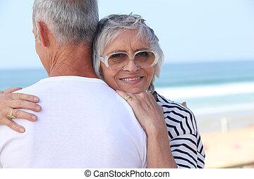 Elderly couple hugging by a beach