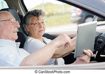Elderly couple in car, looking at sat nav