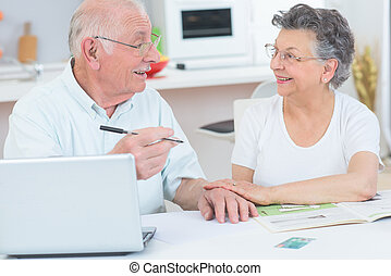 elderly couple in front of the laptop