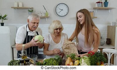 Elderly couple in kitchen receiving vegetables from ...
