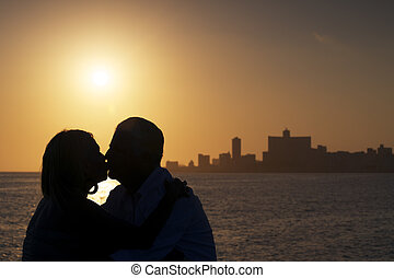 Elderly couple in love, honeymoon with old man and woman kissing near the sea at sunset in La Habana, Cuba. Silhouette of couple and skyline of the city