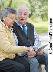 elderly couple in the park with a tablet
