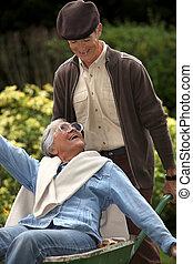 Elderly couple in wheelbarrow