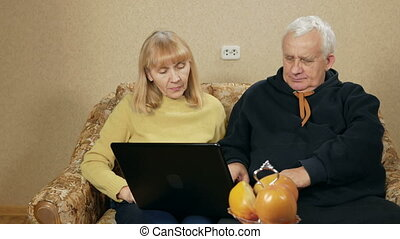 Elderly couple learn how to work with laptop. A man shows how to do it. Woman Laughs and repeats after him. older people learning concept
