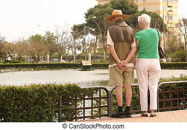 elderly couple looking across the lake