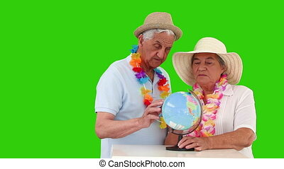 Elderly couple looking at a world globe