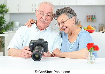 Elderly couple looking at photos on display of digital camera