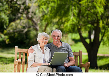 Elderly couple looking at their lap