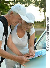 Elderly couple looking at travel map