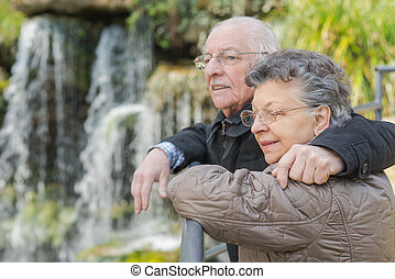 Elderly couple looking at view of waterfall