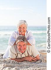 Elderly couple lying down on the beach