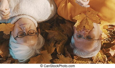 Elderly couple lying on the forest ground and playing with yellow autumn leaves. Love and romance in old age
