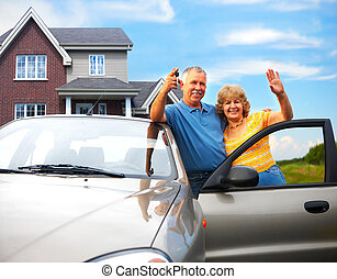 Elderly couple near their home. Real estate and insurance...