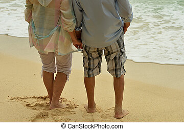 elderly couple on beach together. Back view