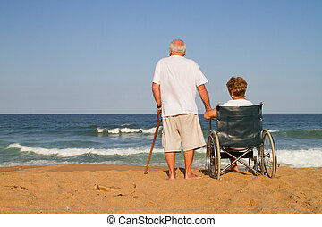 elderly couple on beach - wife sitting on wheelchair - view...