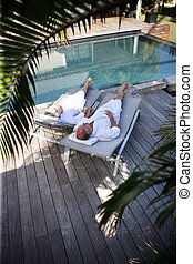 Elderly couple on sun loungers by a pool