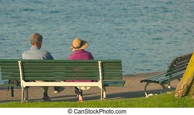Elderly couple on the bench. Seniors near lake, back view.