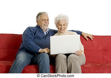 elderly couple on the sofa using a laptop