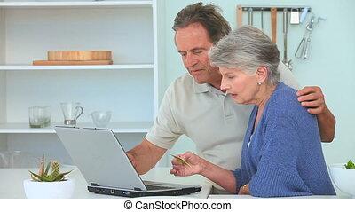 Elderly couple paying something on internet
