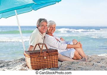 Elderly couple picniking on the bea