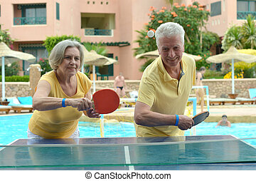 Elderly couple playing ping pong
