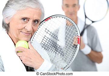 Elderly couple playing tennis