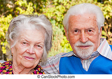 Portrait of an elderly couple sitting outdoors.