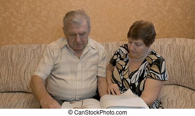 Elderly couple reading a book, on the couch, they are happy together.