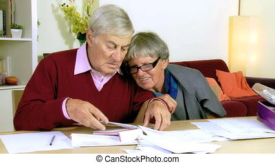 Elderly couple reading documents