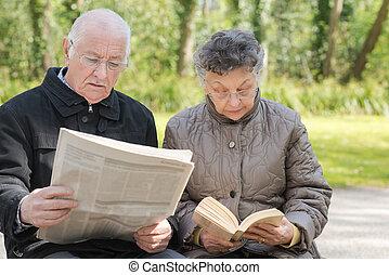 Elderly couple reading outdoors