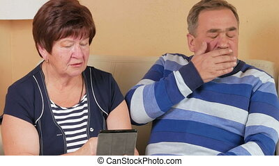 Elderly couple receives doctor consultation for tablet PCs. Man coughs and the doctor gives advice on the internet. Husband and wife sitting in a beautiful house on the couch