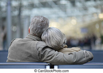Elderly couple relaxing on a bench. back view