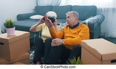 Elderly couple relocating to new home. Woman using VR glasses to preview design. High quality 4k footage