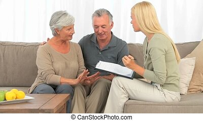 Elderly couple responding to few questions on a sofa