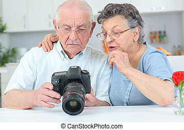 Elderly couple reviewing photos on display on digital camera