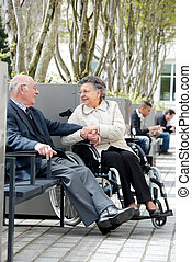 Elderly couple sat outside, woman in wheelchair