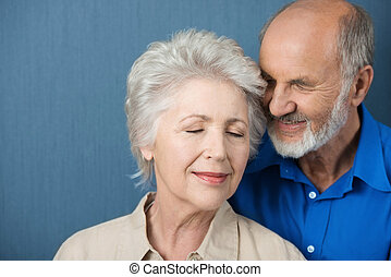 Elderly couple share a tender moment of love as they stand...